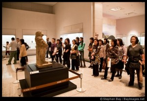 Visitors to the National Museum of Korea gather around a stone zodiacal figurine representing a monkey from the 8th century.