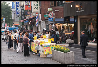Shoppers on a busy sidewalk in Seoul.